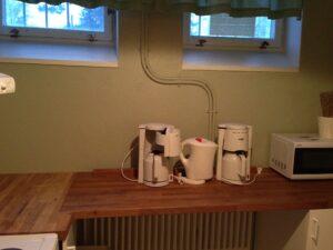 En bra arbetsbänk finns i köket och vattenkokare sam kaffebryggare med termosar.